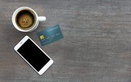 Bewegliches intelligentes Telefon und Kreditkarte auf hölzernem Beschaffenheitshintergrund Stockbilder