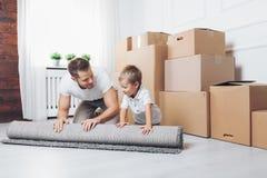 Bewegliches Konzept, Vater und Sohn, die auf ein neues Haus umziehen stockbild