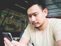 Bewegliches Phon des Manngebrauches im Café stockfotos