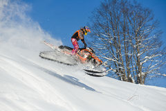 Bewegliches Schneemobil fahrung im Winterwald in den Bergen lizenzfreie stockfotos
