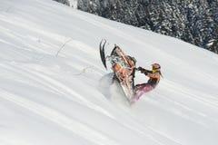 Bewegliches Schneemobil fahrung im Winterwald in den Bergen stockbilder