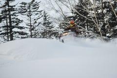 Bewegliches Schneemobil fahrung im Winterwald in den Bergen lizenzfreies stockbild