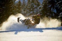 Bewegliches Schneemobil fahrung im Winterwald in den Bergen stockfotografie