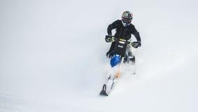 Bewegliches Schneemobil fahrung im Winterwald in den Bergen lizenzfreies stockfoto
