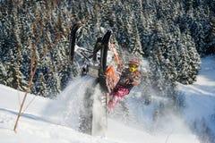 Bewegliches Schneemobil fahrung im Winterwald in den Bergen stockfoto