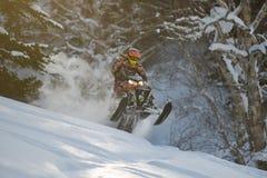 Bewegliches Schneemobil fahrung im Winterwald in den Bergen stockbild