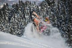 Bewegliches Schneemobil fahrung im Winterwald in den Bergen stockfotos