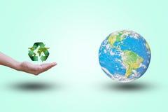 Bewegliches Wiederverwertungssymbol öffnet aufschlussreiche grüne Blätter Welt auf einem Pastellhintergrund farbe umgebung Konzep Stockfotografie