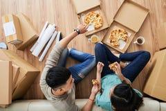 Bewegt in die Paare des neuen Hauses, die Pizza essen lizenzfreie stockfotos