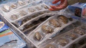 Bewegung der Frau gefrorene ganze Ohrschnecke am Meeresfrüchteabschnitt kaufend stock footage