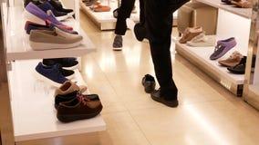 Bewegung der Frau versuchend auf neuen schwarzen Turnschuhen im Schuhgeschäft stock footage
