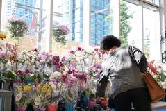 Bewegung der kaufenden Orchidee der Leute auf Anzeigenblumengestell innerhalb des intelligenten Speichers des Preises Nahrungsmit Stockfotografie