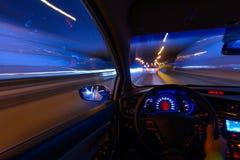 Bewegung des Autos nachts auf der Landlandstraße an einer hohen Geschwindigkeit der Betrachtung vom Innere mit dem Fahrer Hand an lizenzfreie stockbilder