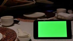 Bewegung des grünen Schirmtelefons mit den Unschärfeleuten, die Menü betrachten stock video footage