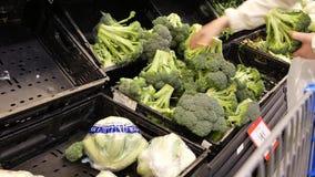 Bewegung des kaufenden Brokkolis der Frau innerhalb Walmart-Speichers stock footage