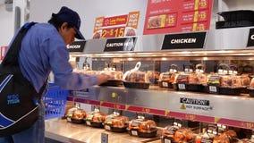 Bewegung des Mannes gebratenes reifes Huhn innerhalb Walmart-Speichers vorwählend stock footage