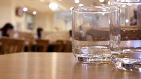 Bewegung des Trinkwassers der Leute mit den Unschärfeleuten, die Nahrungsmittel essen stock footage