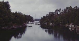 Bewegung entlang Fjord durch Häuser auf Küstenyachten auf dunklem Wasser stock footage