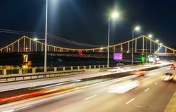 Bewegung von Autos in der Nacht vor dem hintergrund der Brücke lizenzfreie stockfotografie