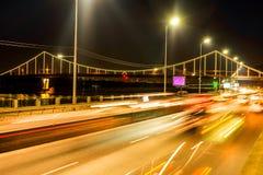 Bewegung von Autos in der Nacht vor dem hintergrund der Brücke lizenzfreies stockfoto