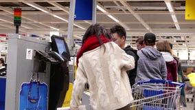 Bewegung von den Leuten, die den Empfang am Eigentest heraus zahlen und nehmen, widersprechen innerhalb Ikea-Speichers stock video
