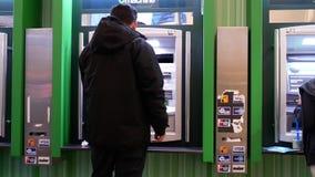 Bewegung von den Leuten, die Geld an ATM-Maschine zurücknehmen stock footage