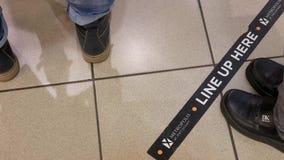 Bewegung von den Leuten, die hier vor Zeichen der Anordnung auf Boden für kaufenden Käsekuchen umziehen stock footage