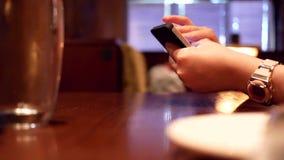 Bewegung von den Leuten, die Mitteilung auf iphone lesen und heißen Tee gießen stock video