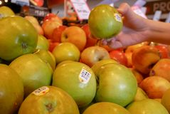 Bewegung von Frau ` s Hand, die organischen Ambrosiaapfel innerhalb des Supermarktes auswählt Stockbild