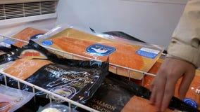Bewegung von Frauenkaufenden Lachsfischen am Meeresfrüchteabschnitt stock footage