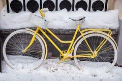 Bewegungsloses gelbes Fahrrad mit weißen Rädern und Korb im Sn Lizenzfreies Stockfoto
