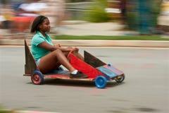 Bewegungsunschärfe des Mädchen-Lenkautos im Seifenkistenrennen Lizenzfreies Stockbild