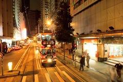Bewegungsunschärfen von gehendem nahem Halt der Leute der Doppeldecker-Straßenbahn auf Nachtstraße Stockfotografie
