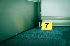 Beweisen Sie Markierung Nr. 7 auf Teppichboden nahe vermutlich defektem Gegenstand herein Stockbilder
