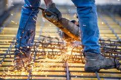 Bewerkt het arbeiders scherpe staal, zagende versterkte bars die hoekmolen met behulp van zaag in verstek Royalty-vrije Stock Foto's