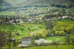 Bewerkt het de lente landbouwlandschap met al type van bloesembomen in tuin onder heuvels - Coöperatieve vereniging - op de foto  Royalty-vrije Stock Afbeelding