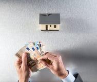 Bewertung des Gebäudes mit den Händen des Geschäftsmannes, des Schlüssels und des Geldes Stockfoto