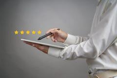 Bewertung mit fünf Sternen oder Klassifizierung, Benchmarkingkonzept Mann mit Tablet-PC setzt Service, Hotel, Restaurant fest stockfotografie