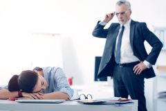 Bewildered chief looking at his employee sleeping at work Stock Image
