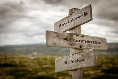 Bewildered, disoriented and unclear text on wooden signpost outdoors in nature. stock photography