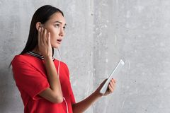 Bewildered elegant girl is having unpleasant conversation. Communication problems. Grieved young asian woman in earphones is holding tablet and touching ear Stock Photos
