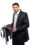 Bewildered handsome man. In black suit and choice of ties Stock Photography