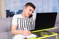 Bewildered handsome young man working on a laptop Stock Photo