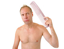 Bewildered man hand holding comb on the head Stock Images