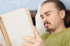 Bewildered man reading book. Bewildered young caucasian man reading vintage book Stock Images