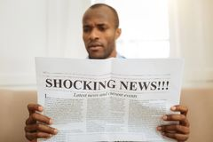 Bewildered man reading shocking news. Being astonished. Serious astonished afro-american man holding a newspaper and reading shocking news while sitting on the Royalty Free Stock Images