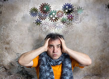 Bewildered Man Releasing Thought Train of Cogs. Bewildered looking man is releasing a thought train of cog wheels. Concerned facial expression. Both hands Stock Photography