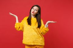Bewildered perplexed young woman in yellow fur sweater spreading, pointing hands aside isolated on bright red wall. Background in studio. People sincere royalty free stock photo