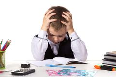 Bewildered pupil sitting with lowered eyes at the desk with hands over the head surrounded with stationery.  royalty free stock image