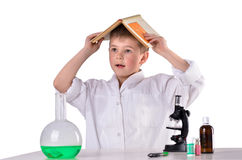 Bewildered scientist boy with book on his had on white background. In the lab Stock Photo